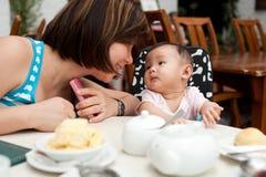 Moder och barn på den äta middag tabellen royaltyfria bilder