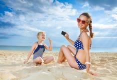 Moder och barn på stranden som tar fotoet med den digitala kameran Arkivfoto