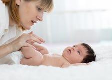 Moder och barn på vit säng Förälder och liten unge som hemma kopplar av Mamman som gör massage, behandla som ett barn arkivfoto