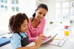 Moder och barn som använder den Digital minnestavlan för läxa Arkivbild