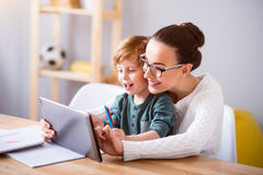 Moder och barn som använder en minnestavla arkivfoton