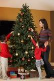 Moder och barn som dekorerar julgranen Fotografering för Bildbyråer