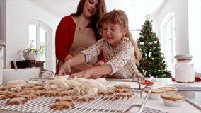 Moder och barn som förbereder julkakor arkivfilmer
