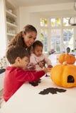 Moder och barn som gör allhelgonaaftongarneringar hemmastadda royaltyfria bilder