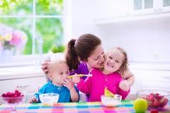 Moder och barn som har frukosten Arkivfoton