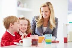 Moder och barn som har frukosten i kök tillsammans Royaltyfri Foto