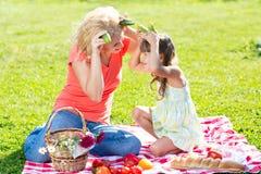 Moder och barn som har gyckel som har picknick på gräs Arkivbild