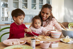 Moder och barn som hemma dekorerar kakor tillsammans royaltyfri bild