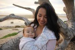 Moder och barn som ler på stranden arkivfoton