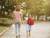Moder och barn som rymmer h?nder som g?r att skola royaltyfri bild