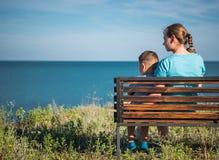 Moder och barn som ser havet Arkivbild