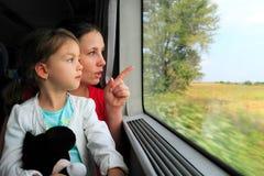 Moder och barn som ser på drevfönstret Royaltyfri Fotografi