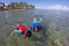 Moder och barn som snorklar över en korallrev Fiji arkivfoton