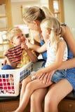Moder och barn som sorterar tvätterit Arkivfoto