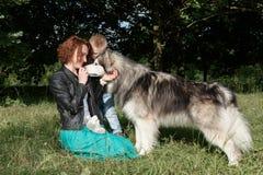Moder och barn som spelar med hunden på naturen Fotografering för Bildbyråer