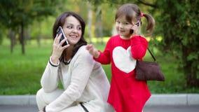 Moder och barn som talar på telefonen