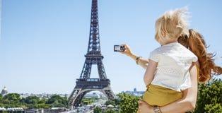 Moder och barn som tar fotoet med kameran mot Eiffeltorn Royaltyfri Bild
