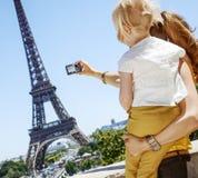 Moder och barn som tar fotoet med kameran mot Eiffeltorn Royaltyfri Foto