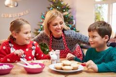 Moder och barn som tillsammans dekorerar julkakor Arkivbilder
