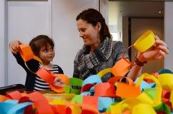 Moder och barn som tillsammans förbereder en handcraftgarnering Royaltyfria Foton