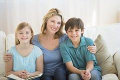 Moder och barn som tillsammans ler på soffan Arkivfoto
