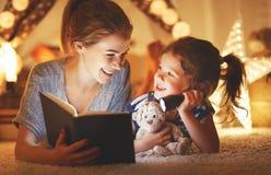 Moder- och barndotter som för läser en bok och en ficklampa Arkivbild