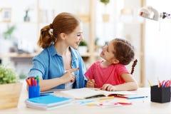 Moder- och barndotter som gör handstil och att läsa för läxa royaltyfria foton