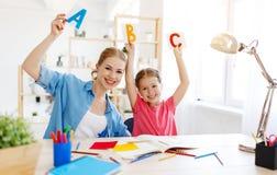 Moder- och barndotter som hemma g?r l?xahandstil och l?sning royaltyfri fotografi
