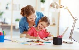 Moder- och barndotter som hemma g?r l?xahandstil och l?sning fotografering för bildbyråer