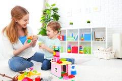 Moder- och barndotter som spelar, byggande från konstruktör Fotografering för Bildbyråer