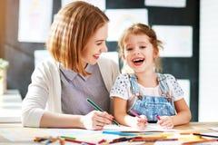 Moder- och barndottern drar i kreativitet i dagis arkivbilder