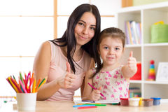 Moder- och barndottern drar samman med blyertspennor på tabellen Arkivbild