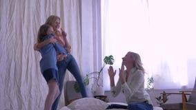 Moder- och barnförhållandet, lyckliga flickor sjunger och dansar anseende på säng framme av mamman hemma stock video