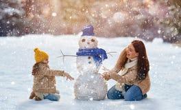 Moder- och barnflickan på en vinter går i natur Arkivfoton