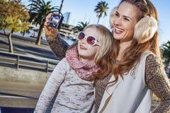 Moder- och barnhandelsresande med den digitala kameran som tar fotoet Fotografering för Bildbyråer