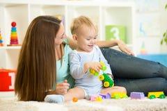 Moder- och barnpojke som tillsammans inomhus spelar Royaltyfria Bilder