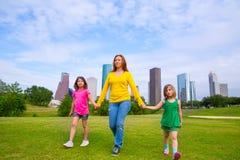 Moder och döttrar som går rymma händer på stadshorisont arkivfoto