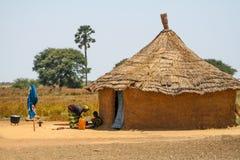 Moder och dother framme av deras hus i Senegal, Afrika Arkivfoto