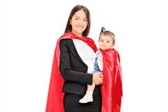 Moder och dotter, i att posera för superherodräkter Arkivfoton
