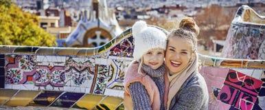 Moder och dotter i Barcelona som kramar, medan sitta på bänk Arkivbild
