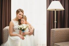 Moder och dotter i de samma bröllopsklänningarna Arkivfoto