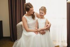 Moder och dotter i de samma bröllopsklänningarna Arkivbild