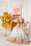 Moder och dotter i den härliga vita aftonkappan som in sitter Royaltyfri Foto