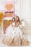 Moder och dotter i den härliga vita aftonkappan som in sitter Royaltyfri Bild