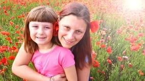 Moder och dotter in i ett fält av vallmo Royaltyfria Bilder