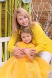 Moder och dotter i guling inomhus royaltyfria bilder