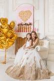 Moder och dotter i härliga vitklänningar som sitter i en chai Royaltyfri Foto