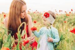 Moder och dotter i härligt vallmofält royaltyfri fotografi