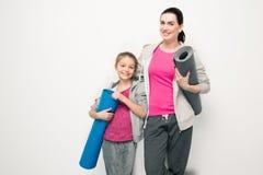 Moder och dotter i hållande yogamats för sportswear och le på kameran arkivfoto