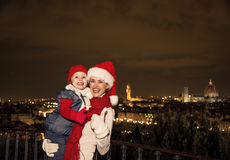 Moder och dotter i julhattar som visar upp tummar, Italien Arkivfoton
